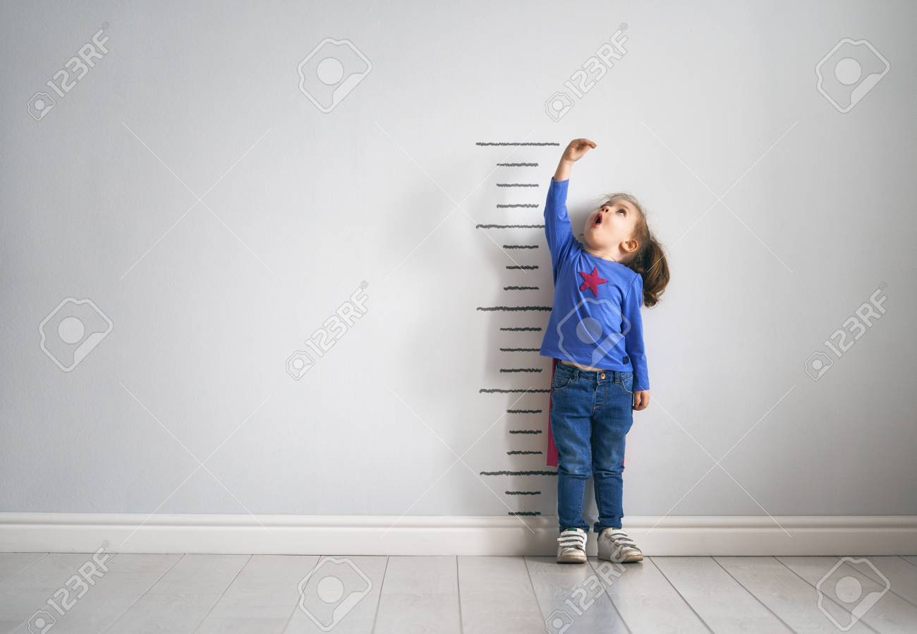 Little child is playing superhero. Kid is measuring the growth on the background of wall. Girl power concept. - 99197356