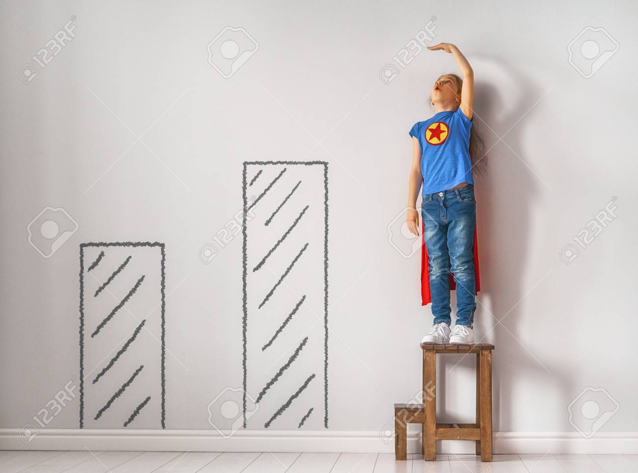 Little child is playing superhero. Kid is measuring the growth on the background of wall. Girl power concept. - 99798514