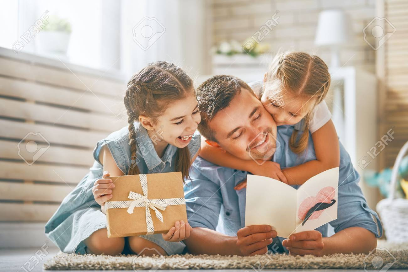 Happy father's day! Children daughters congratulating dad and giving him postcard and gift box. Daddy and girls smiling and hugging. Family holiday and togetherness. - 100746819