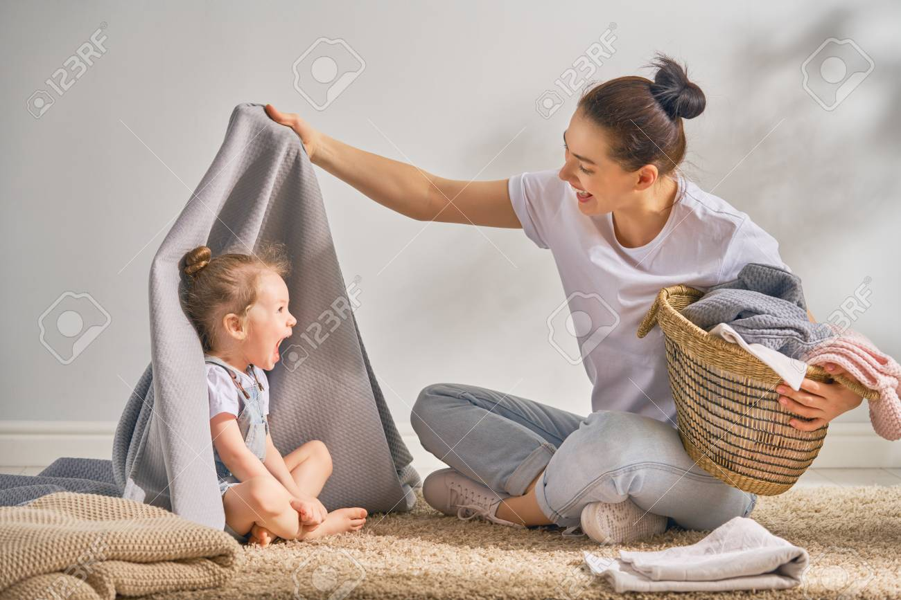 Beautiful young woman and child girl little helper are having fun and smiling while doing laundry at home. - 100750493