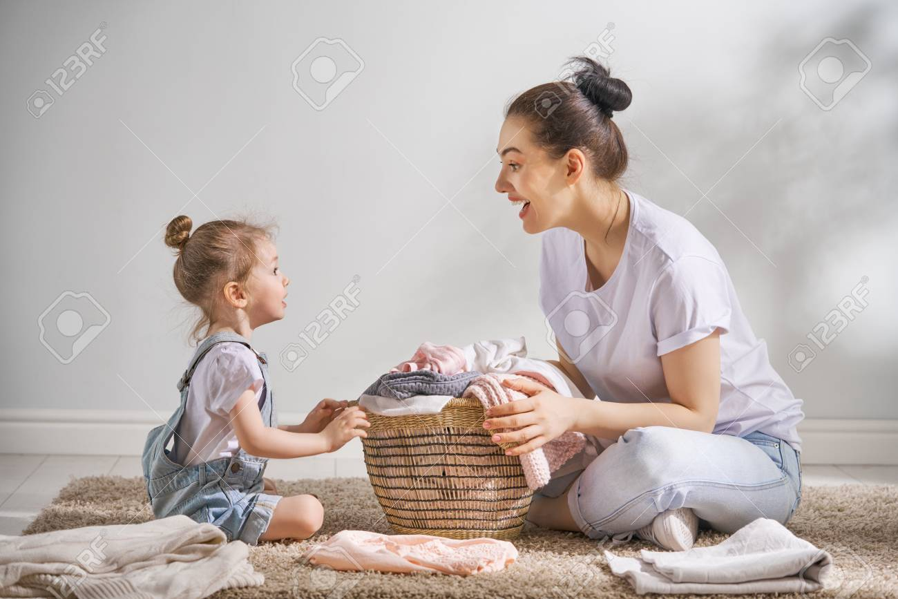 Beautiful young woman and child girl little helper are having fun and smiling while doing laundry at home. - 100750494