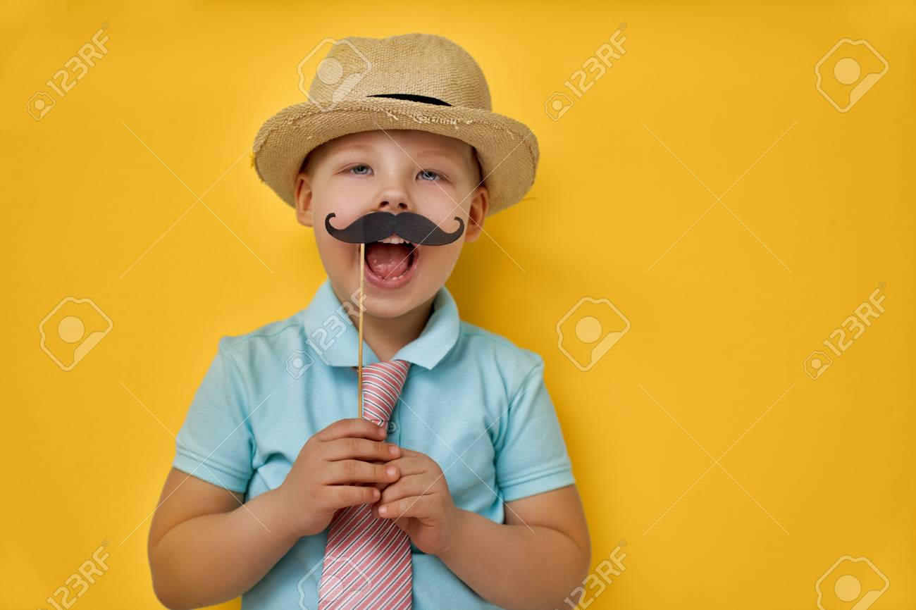 Funny time. Happy father's day! Boy playing and holding paper mustache on stick and pretending of daddy. - 101297900
