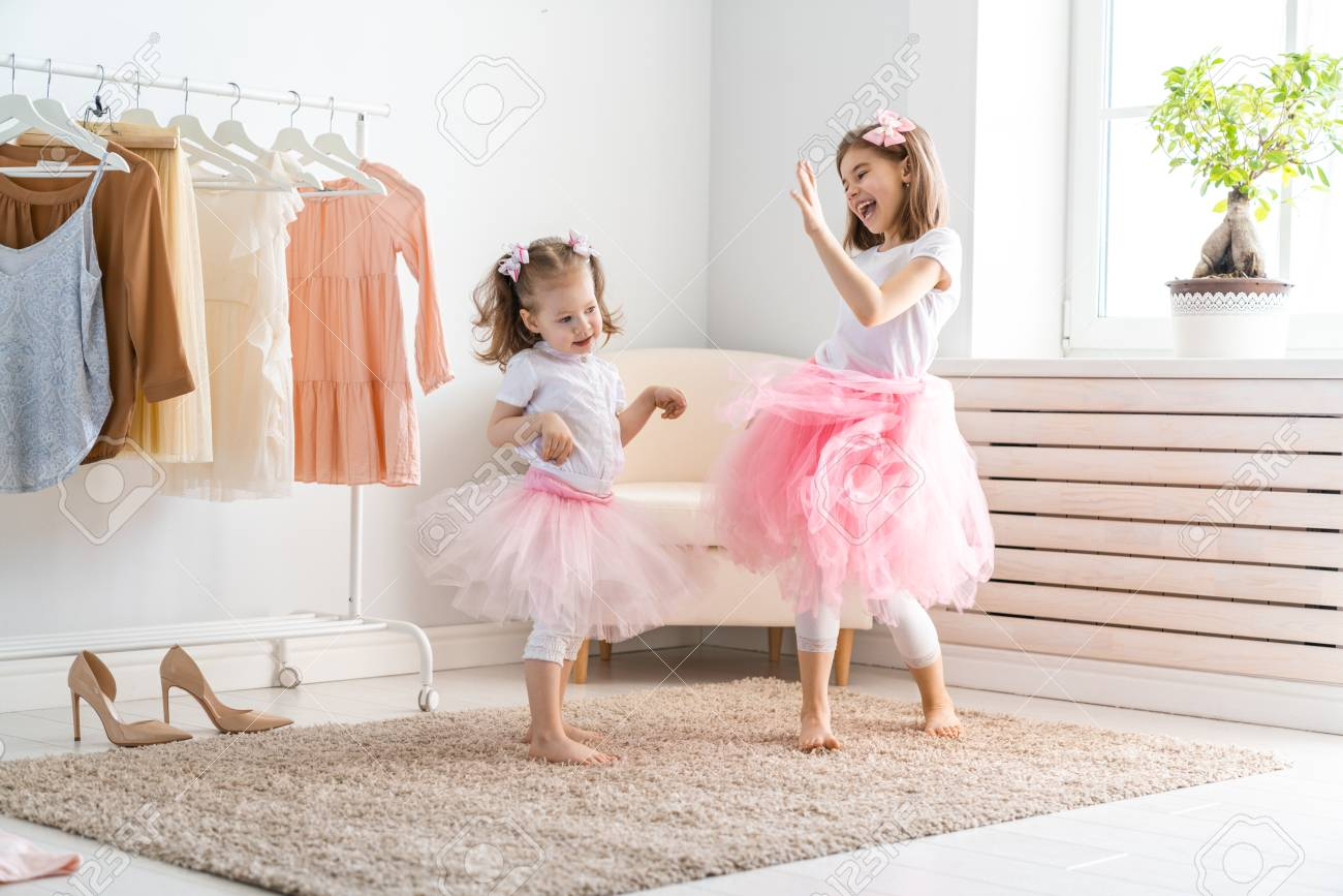 Happy girls dressing up at home. Funny lovely children are having fun in room. - 101969543