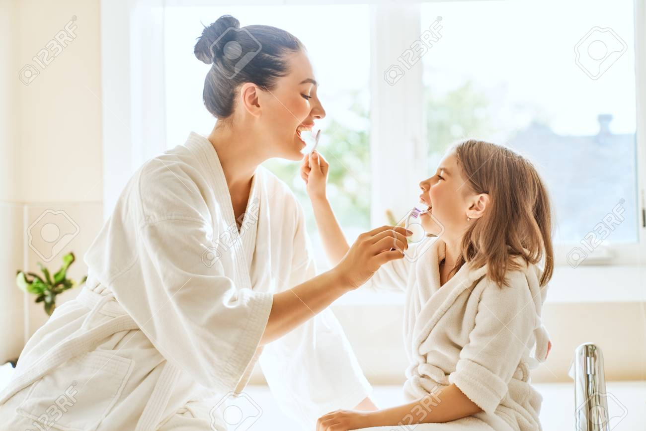 Happy family! Mother and daughter child girl are brushing teeth toothbrushes in the bathroom. - 103091489