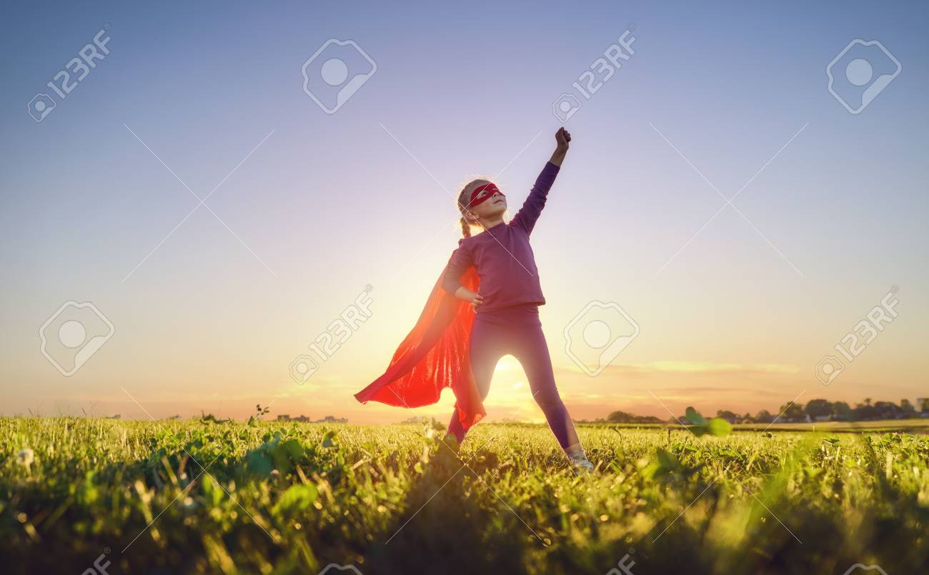 Little child is playing superhero. Kid on the background of sunset sky. Girl power concept - 104771814
