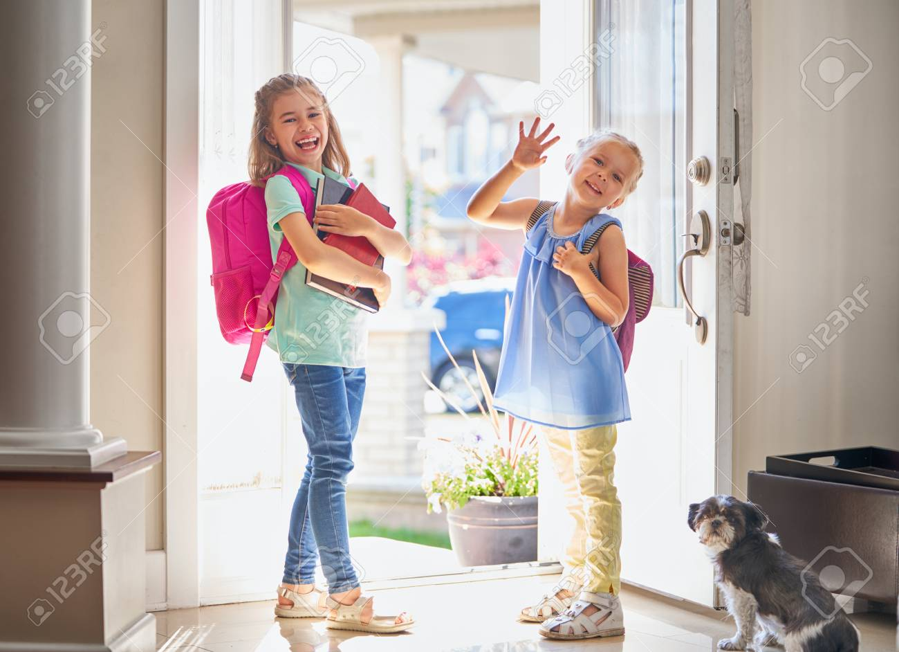 Pupils of primary school. Girls with backpack is going to school from home. Beginning of lessons. First day of fall. - 104771821