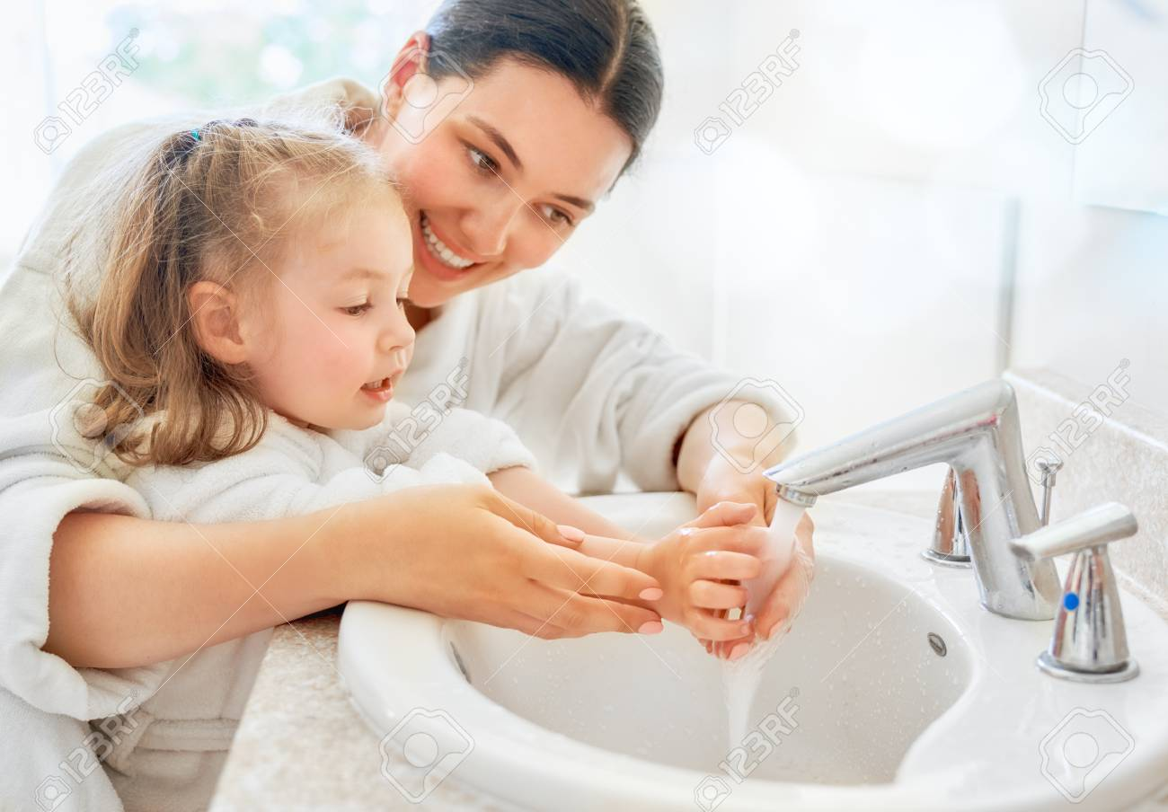 Cute little girl and her mother are washing hands under running water. - 105504226