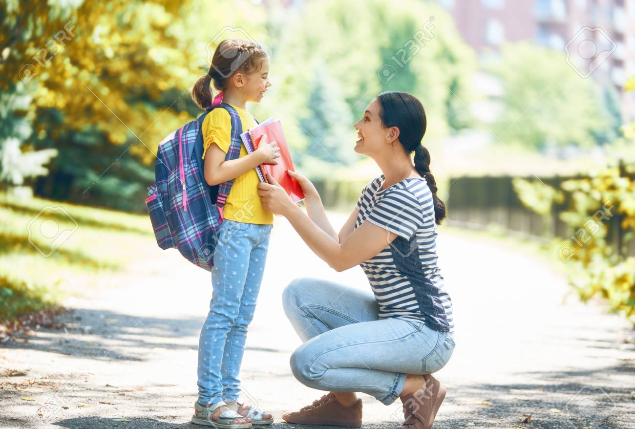 Parent and pupil of primary school go hand in hand. Woman and girl with backpack behind the back. Beginning of lessons. First day of fall. - 106204737