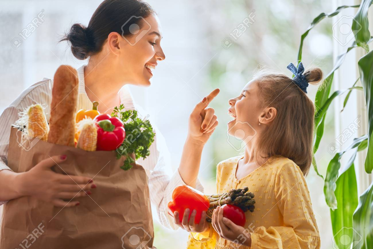 Family shopping. Mother and her daughter are holding grocery shopping bag with vegetables. - 106032815
