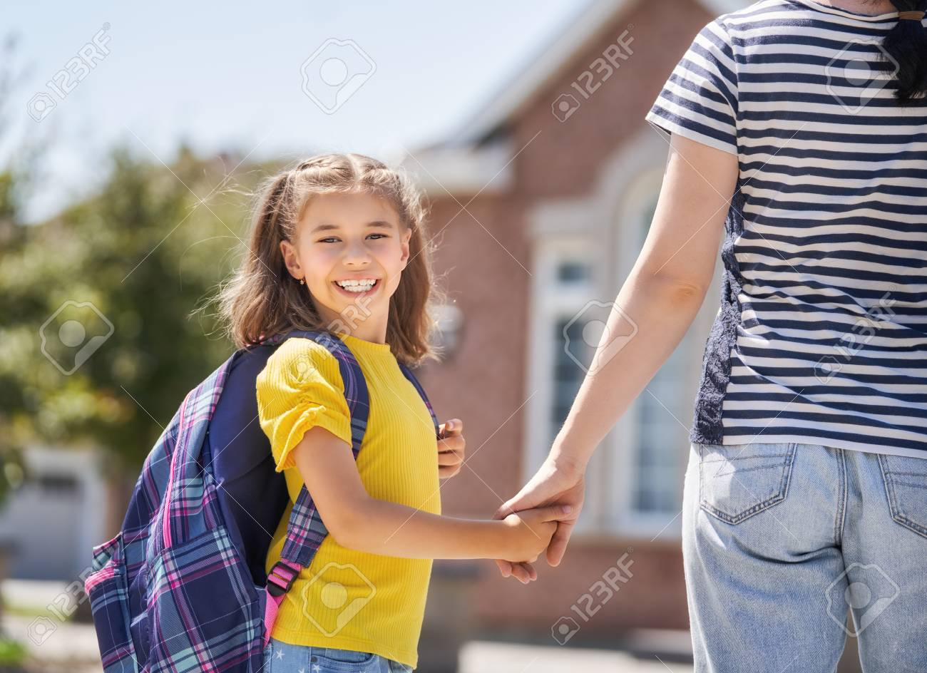 Parent and pupil of primary school go hand in hand. Woman and girl with backpack behind the back. Beginning of lessons. First day of fall. - 106032818