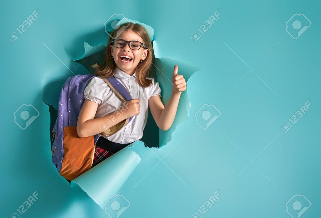 Back to school and happy time! Cute industrious child is breaking through color paper wall. Kid with backpack. Girl ready to study. - 105931619