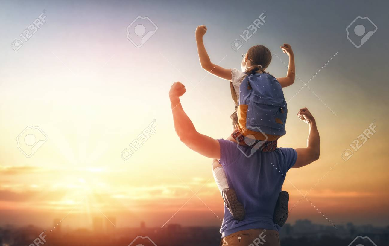 Parent and pupil of primary school on sunset background. Man and girl with backpack behind the back. Beginning of lessons. First day of fall. - 105931621