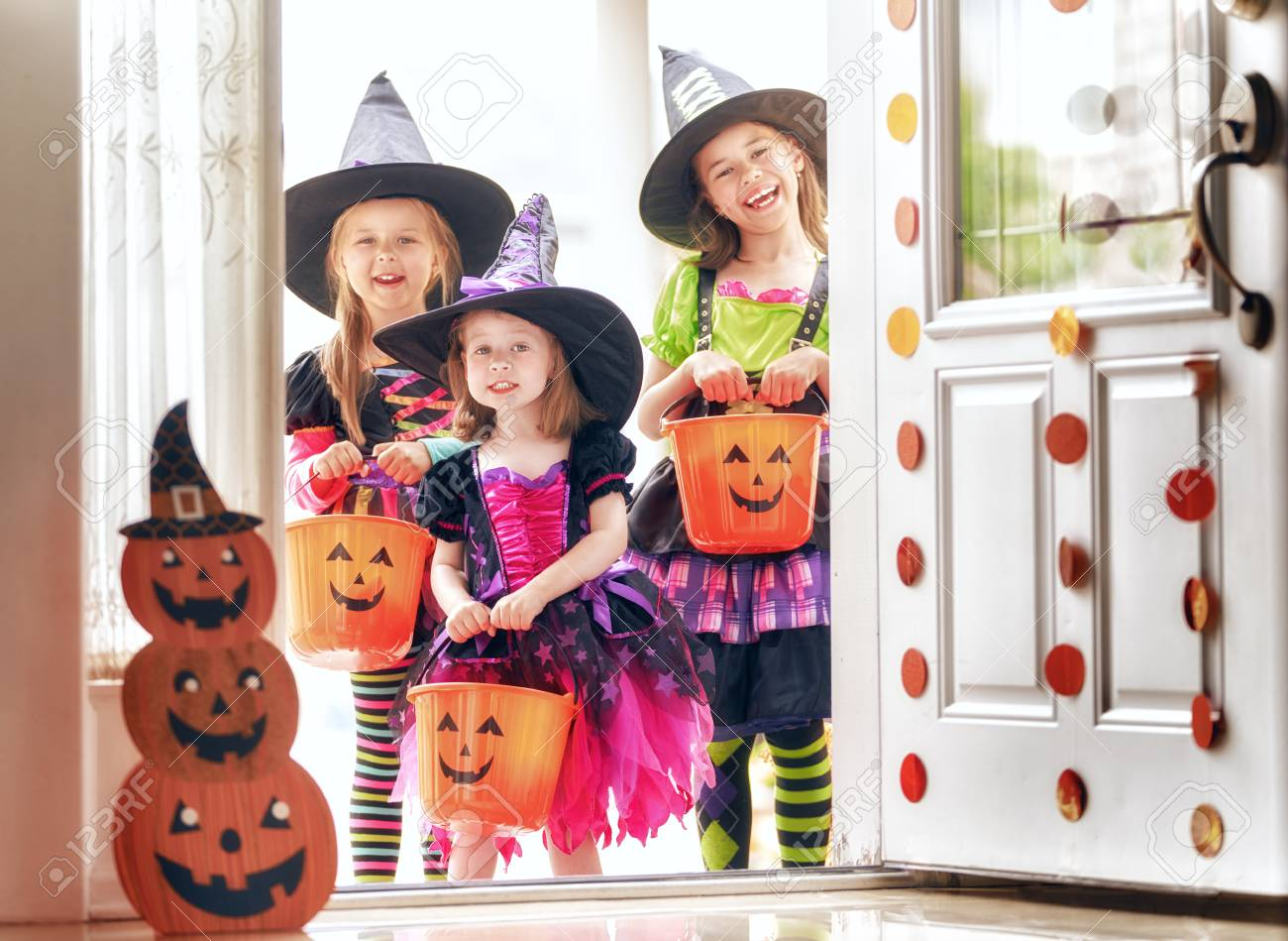 Happy Halloween! Three cute little laughing girls in witches costumes are coming to the house for sweets. - 106387282