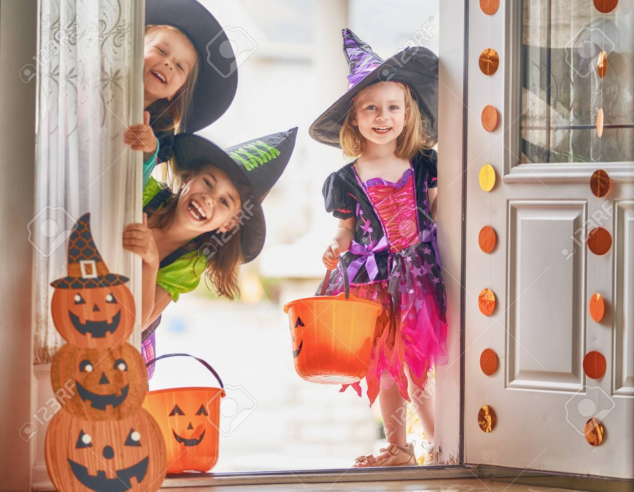 Happy Halloween! Three cute little laughing girls in witches costumes are coming to the house for sweets. - 106387285