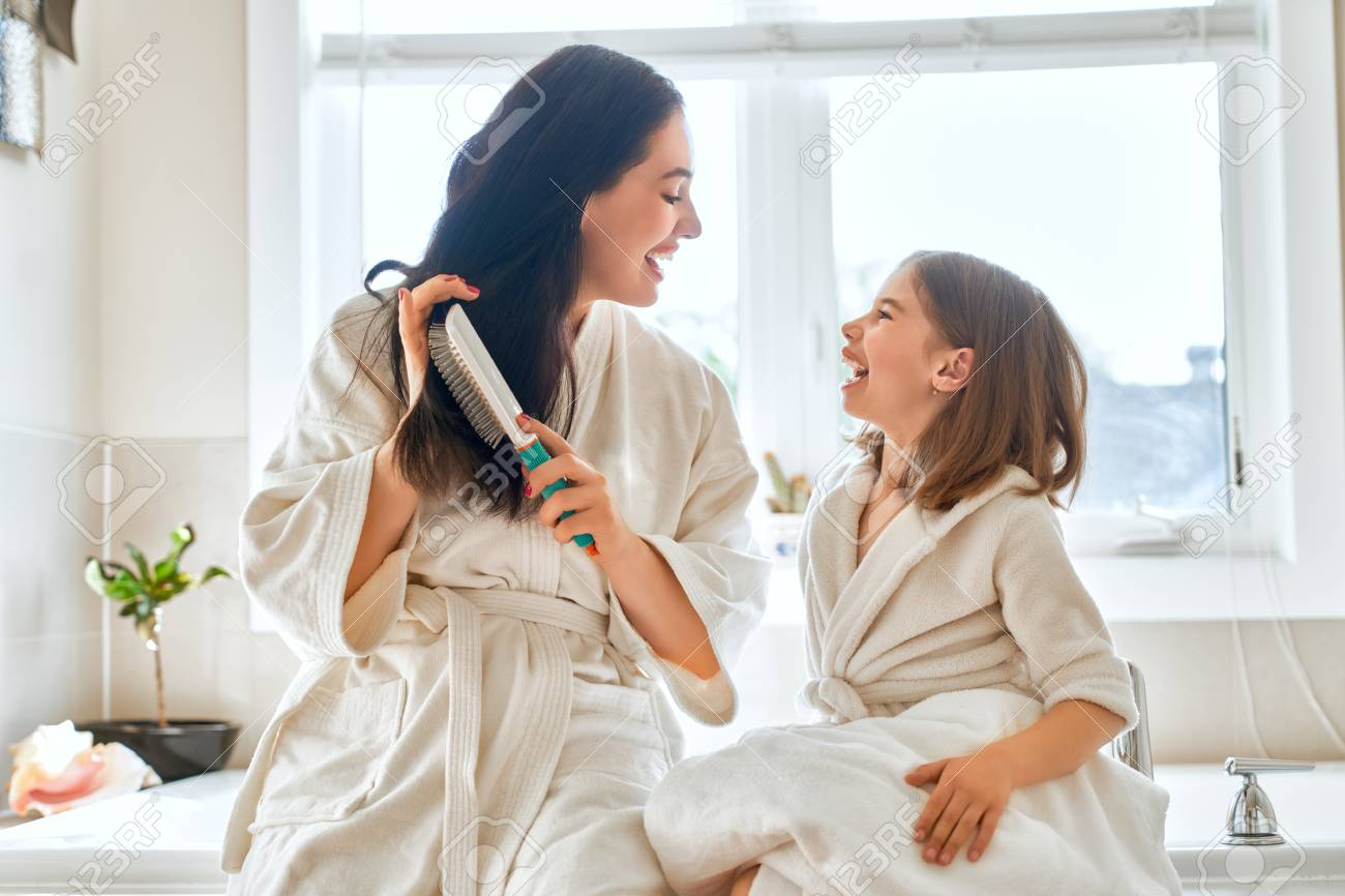 Happy family! Mother and daughter child girl are combing hair in the bathroom. - 106662397