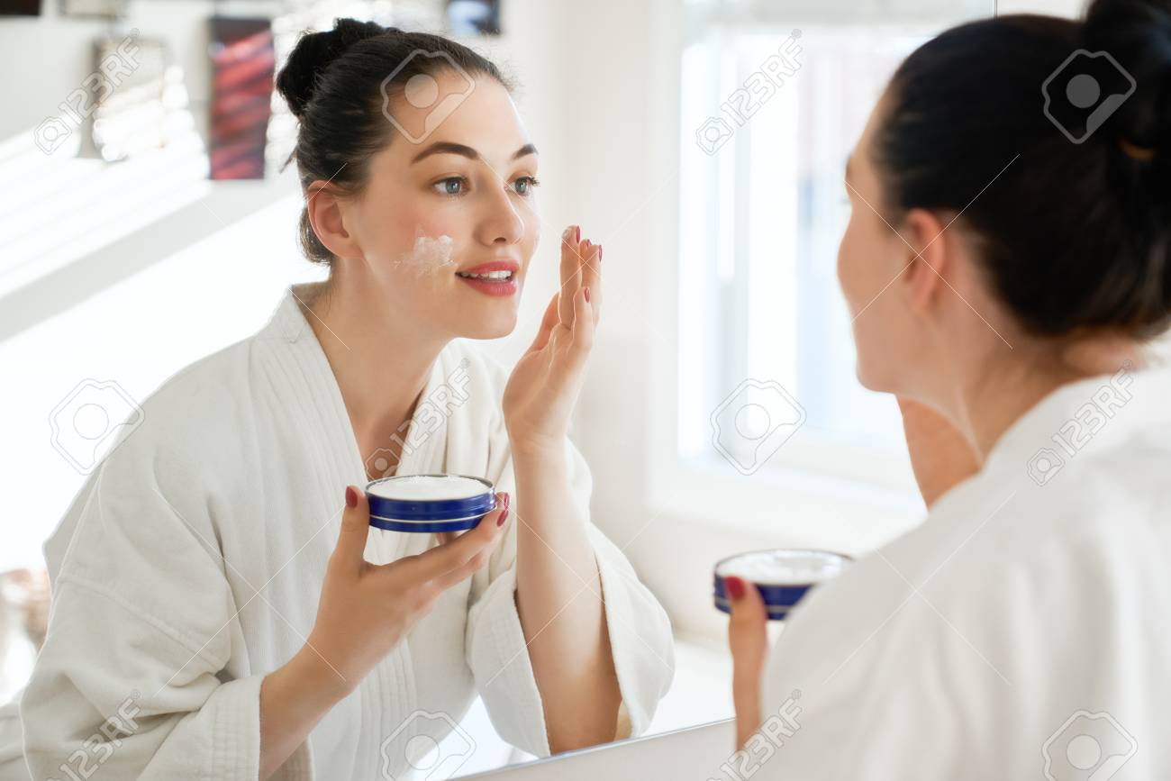 Beautiful young woman with cream for her face looking in the mirror in bathroom at home. Facial treatment. Cosmetology, beauty and spa. - 106662412