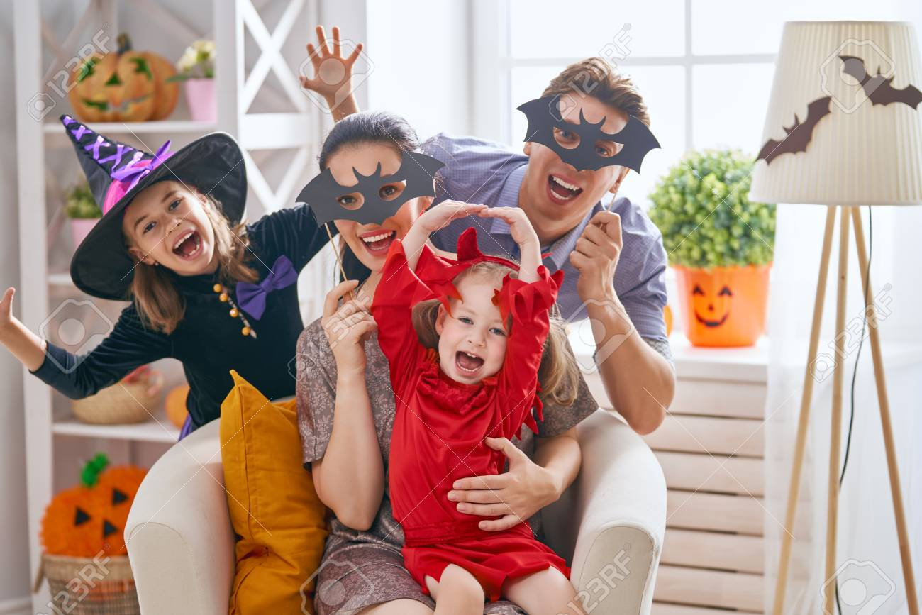 Mother, father and their kids having fun at home. Happy family celebrating Halloween. Children wearing carnival costumes. - 107953119
