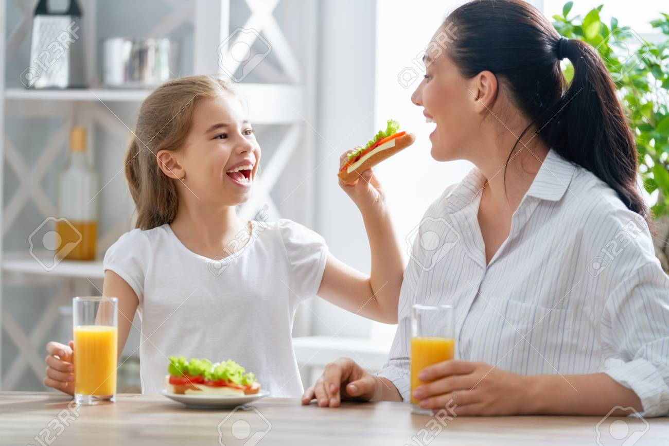 Healthy food at home. Happy family in the kitchen. Mother and child daughter are having breakfast. - 108108325