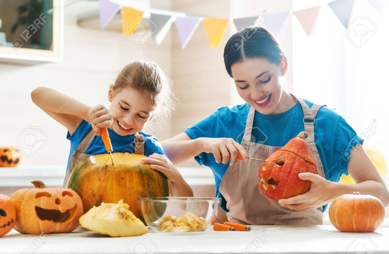 Happy Halloween! Mother and her daughter carving pumpkin. Family preparing for holiday. - 108423489
