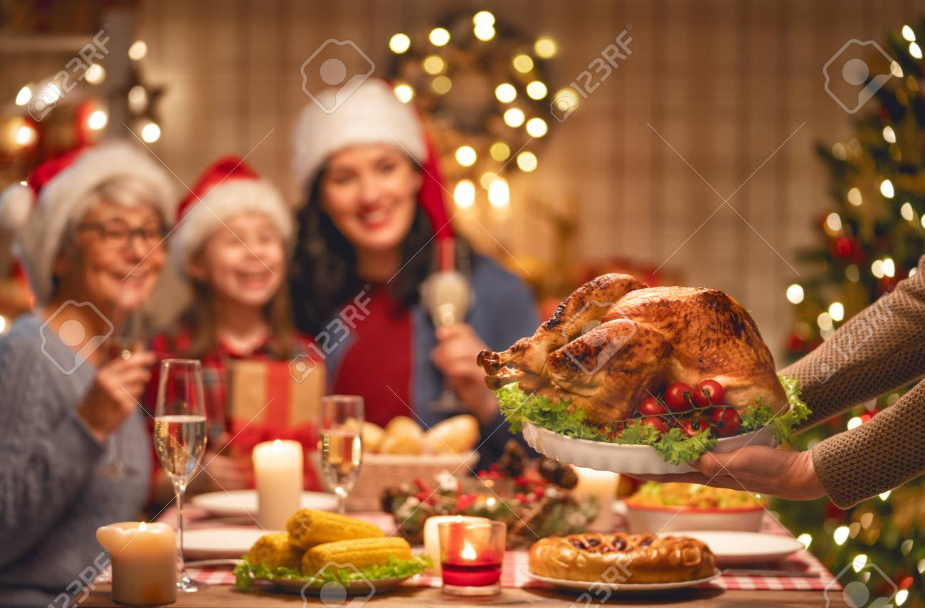 Merry Christmas! Happy family are having dinner at home. Celebration holiday and togetherness near tree. - 112055457