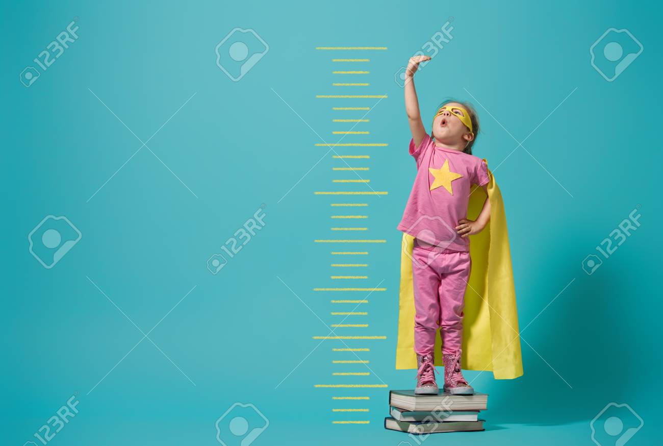 Little child playing superhero. Kid measures the growth on the background of bright blue wall. Girl power concept. Yellow, pink and turquoise colors. - 115374077