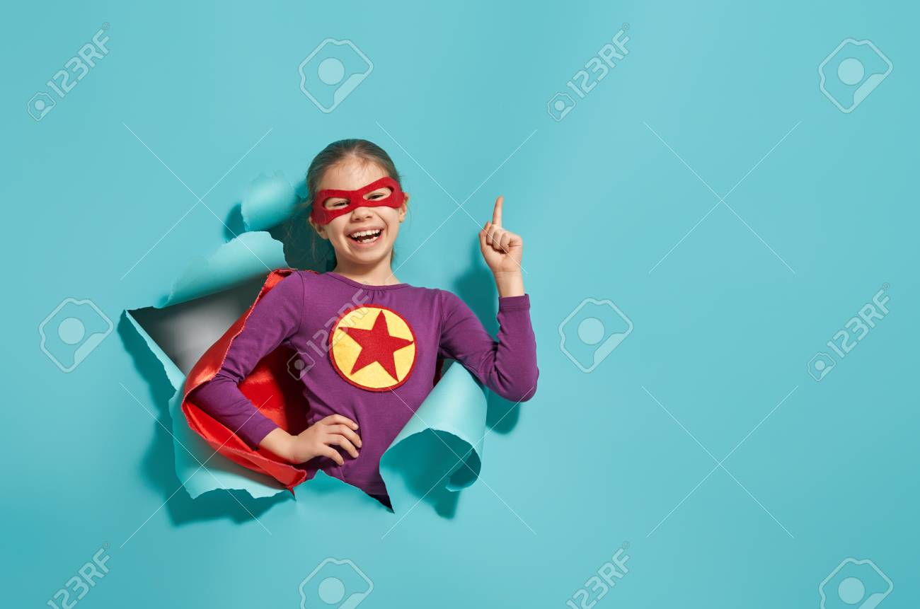 Little child is playing superhero. Kid on the background of bright blue wall. Girl power concept. - 115786425