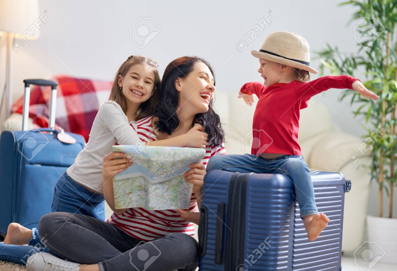 Go on an adventure! Happy family preparing for the journey. Mom and daughters are packing suitcases for the trip. - 115795336