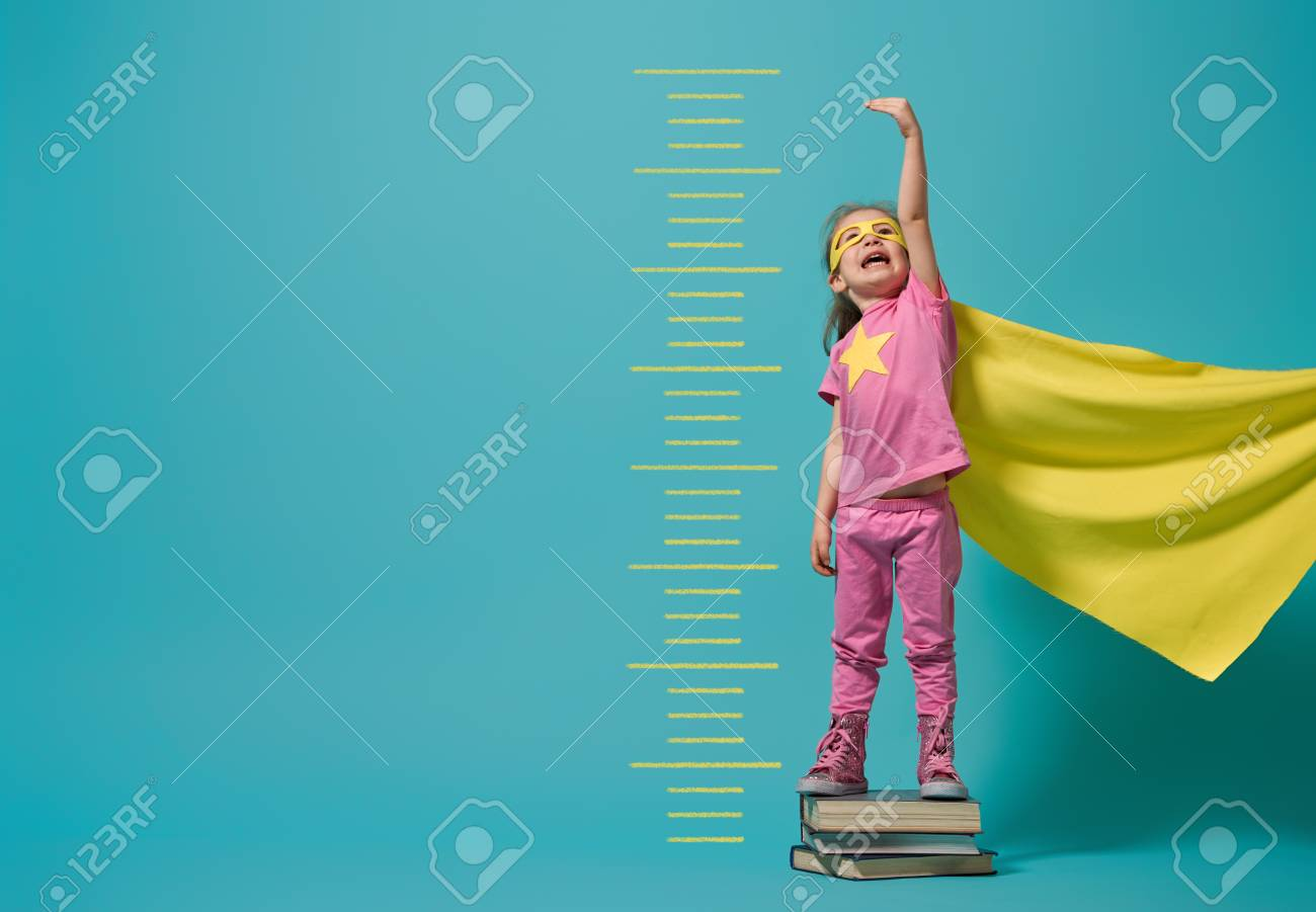 Little child playing superhero. Kid measures the growth on the background of bright blue wall. Girl power concept. Yellow, pink and turquoise colors. - 115812341