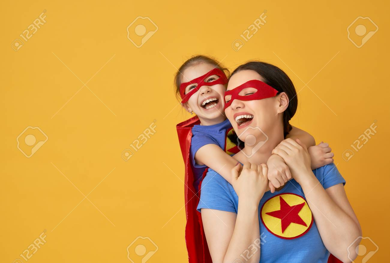 Mother and her child playing together. Girl and mom in Superhero costumes. Mum and kid having fun and smiling. Family holiday and togetherness. - 117184713
