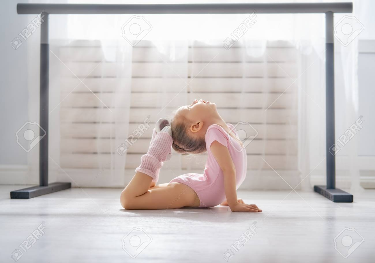 Cute little girl dreams of becoming a ballerina. Child girl in a pink tutu dancing in a room. Baby girl is studying ballet. - 117184765