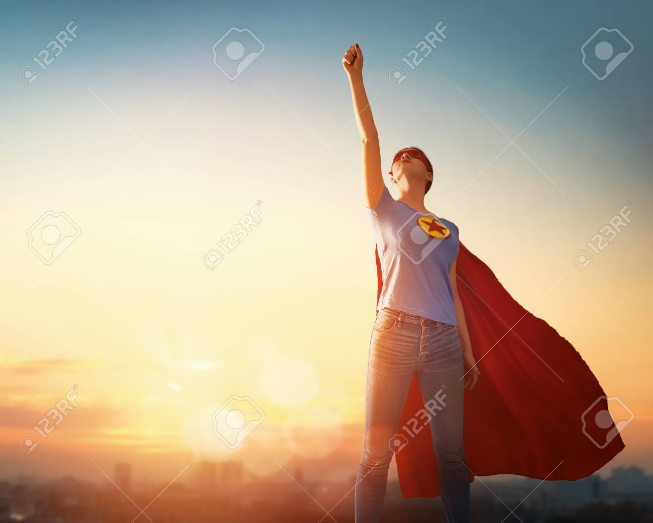 Joyful beautiful young woman in superhero costume posing on sunset background. - 117202637