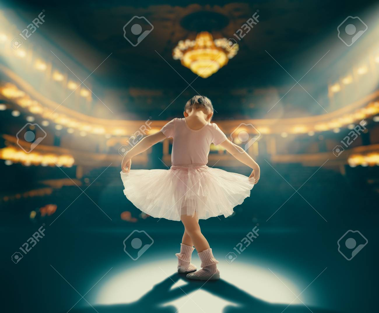 Cute little girl dreaming of becoming a ballerina. Child girl in a pink tutu dancing on the stage. Baby girl is studying ballet. - 117287641