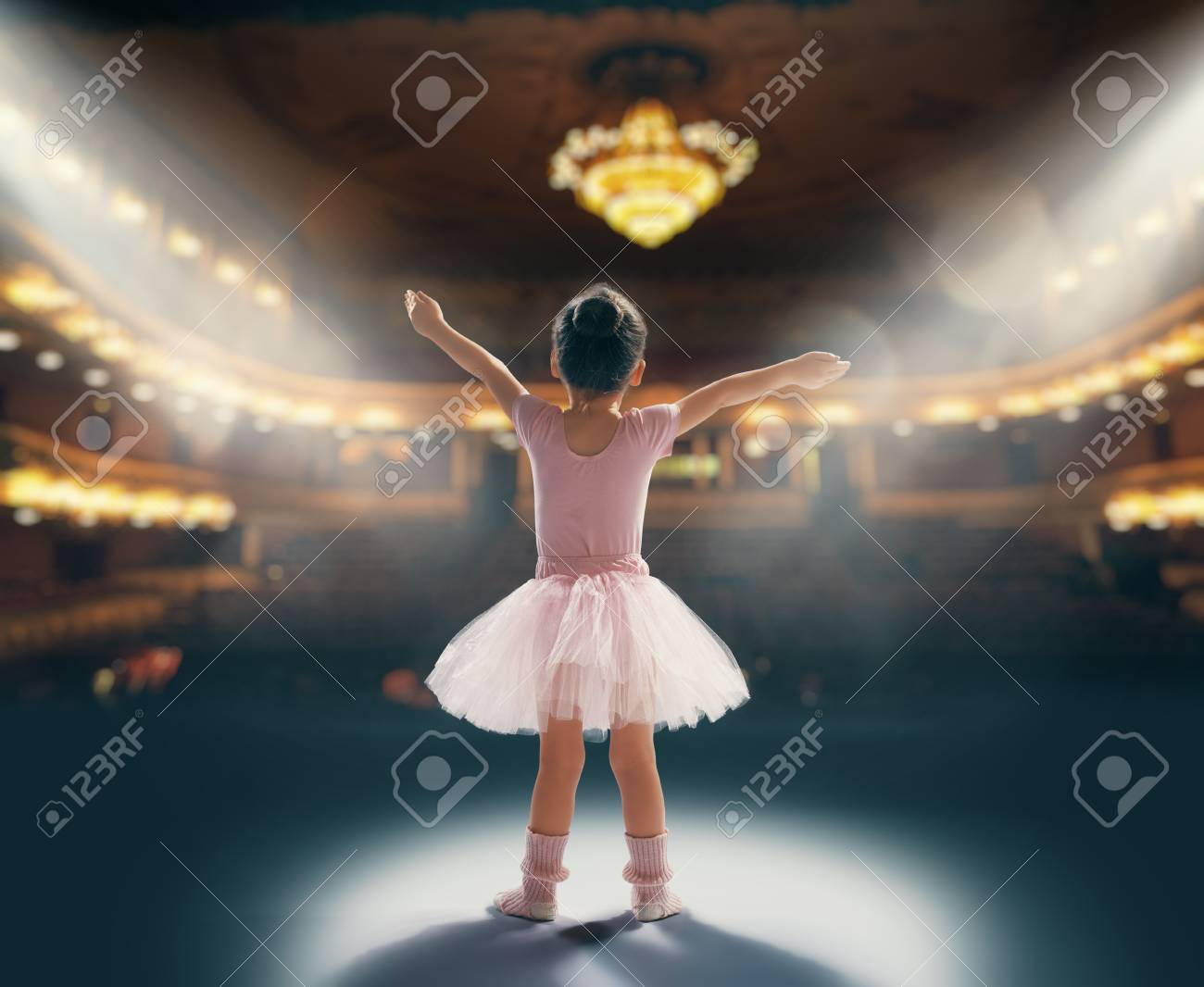 Cute little girl dreaming of becoming a ballerina. Child girl in a pink tutu dancing on the stage. Baby girl is studying ballet. - 117287120
