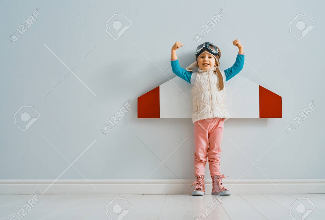 Little child girl in an astronaut costume is playing and dreaming of becoming a spaceman. Portrait of funny kid on a background of grey wall. - 117287167