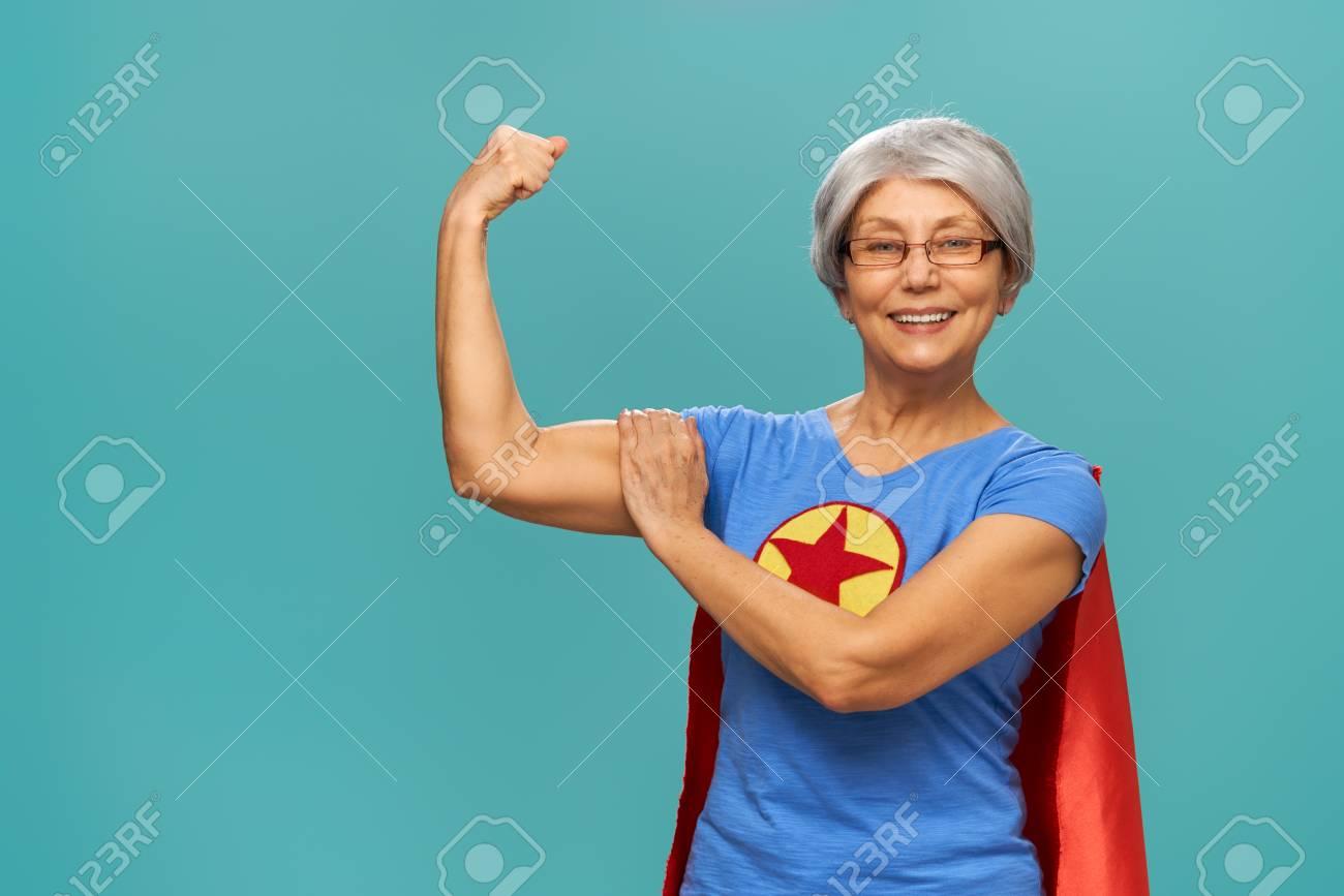 Joyful beautiful senior woman in superhero costume posing on turquoise background. - 117287266