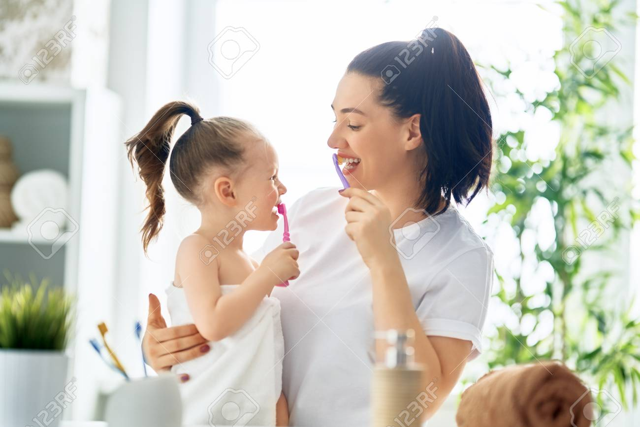 Happy family! Mother and daughter child girl are brushing teeth toothbrushes in the bathroom. - 118459280