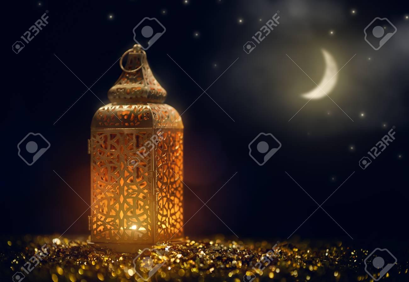 Ornamental Arabic lantern with burning candle glowing at night. Festive greeting card, invitation for Muslim holy month Ramadan Kareem. - 119476666