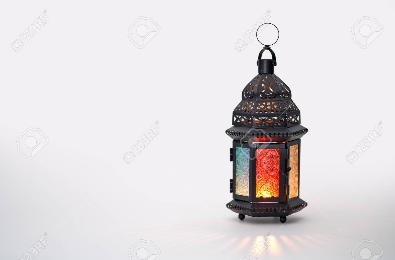 Ornamental Arabic lantern with burning candle glowing on white background. Festive greeting card, invitation for Muslim holy month Ramadan Kareem. - 119476910