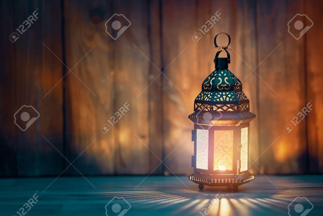 Ornamental Arabic lantern with burning candle glowing at night. Festive greeting card, invitation for Muslim holy month Ramadan Kareem. - 119476928