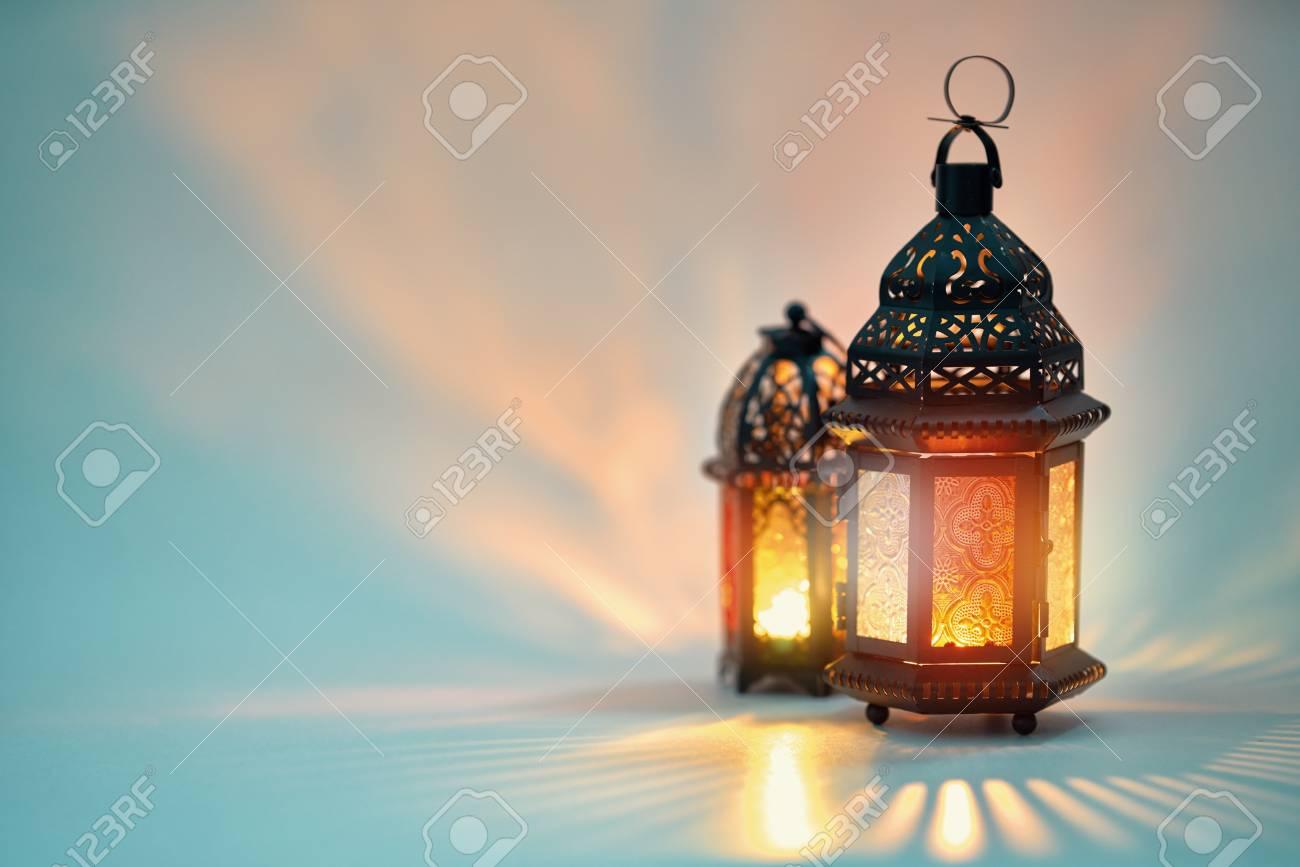 Ornamental Arabic lantern with burning candle glowing on white background. Festive greeting card, invitation for Muslim holy month Ramadan Kareem. - 120575271