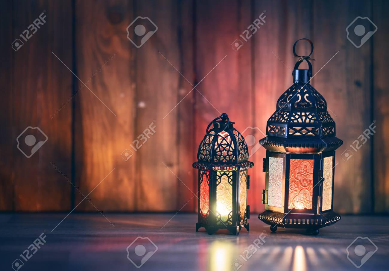 Ornamental Arabic lantern with burning candle glowing at night. Festive greeting card, invitation for Muslim holy month Ramadan Kareem. - 120575281