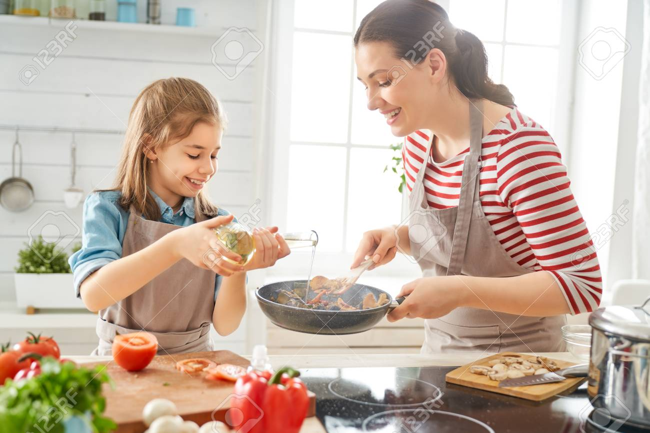 Healthy food at home. Happy family in the kitchen. Mother and child daughter are preparing proper meal. - 123150941