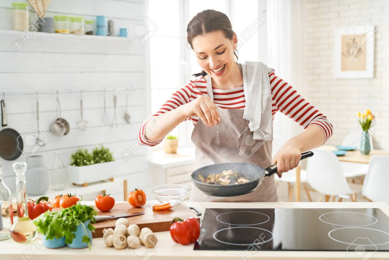 Healthy food at home. Happy woman is preparing the proper meal in the kitchen. - 123151113