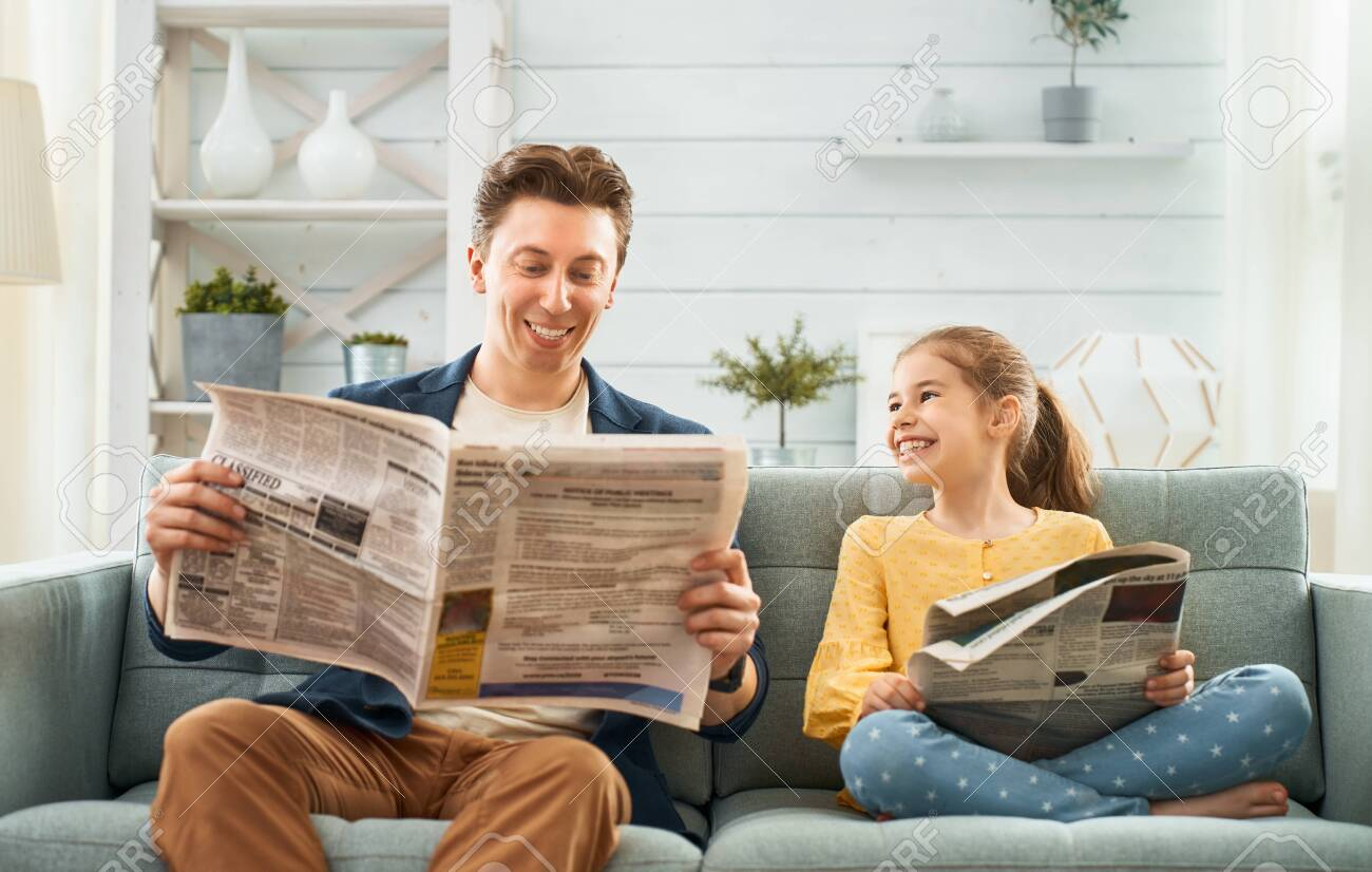 Happy loving family. Daddy and his daughter child girl are reading newspapers together. Father's day concept. - 123391085