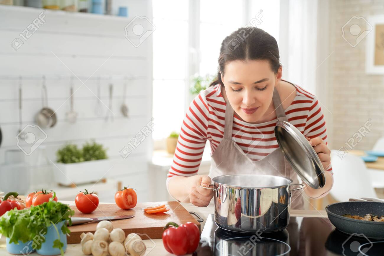 Healthy food at home. Happy woman is preparing the proper meal in the kitchen. - 124256853