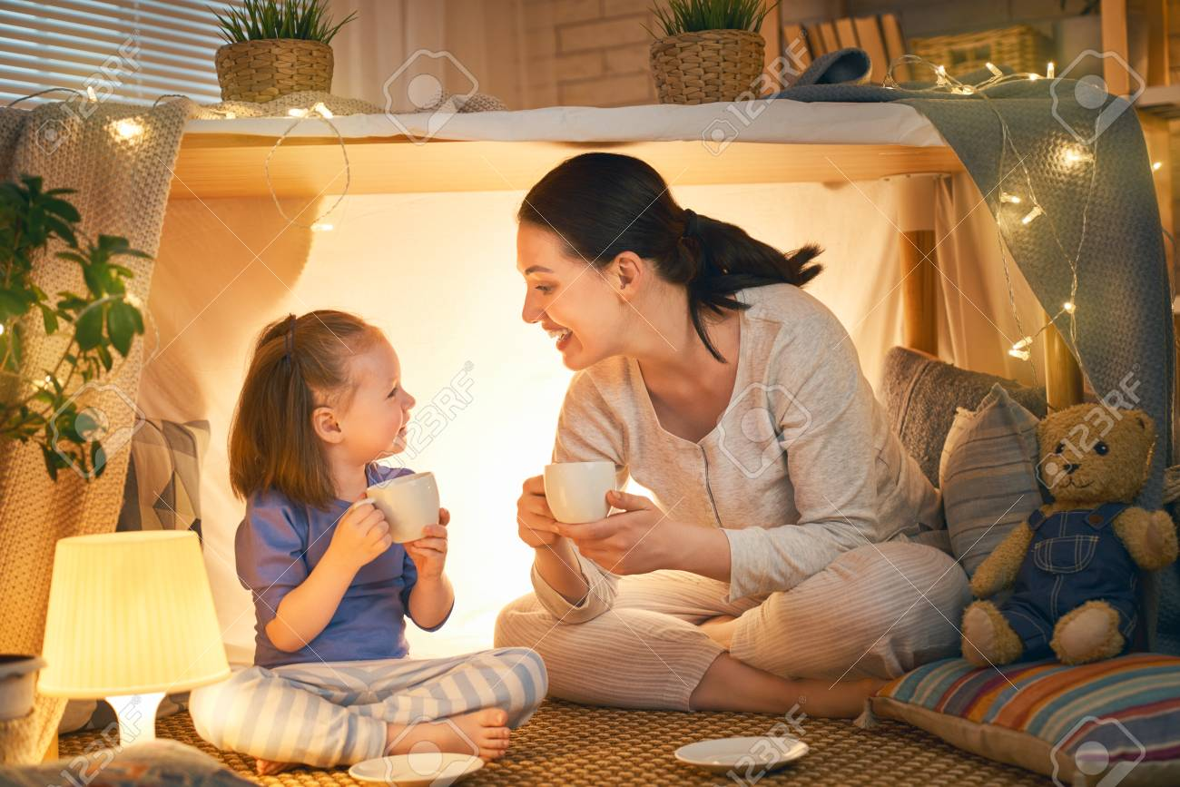 Happy loving family. Mother and her daughter girl play tea-party and drink tea from cups in children room. Funny mom and lovely child having fun indoors. - 124770115