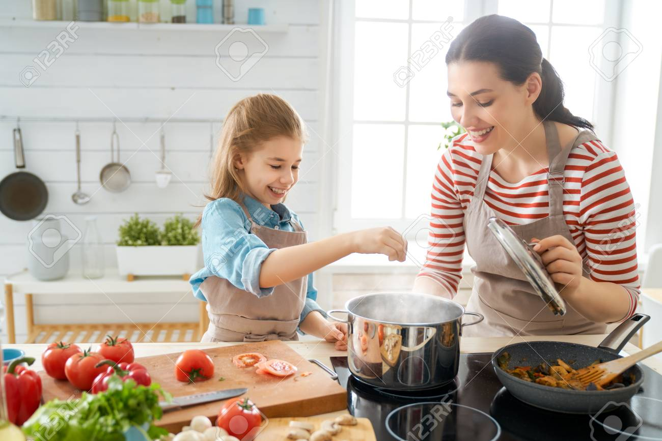 Healthy food at home. Happy family in the kitchen. Mother and child daughter are preparing proper meal. - 124770270