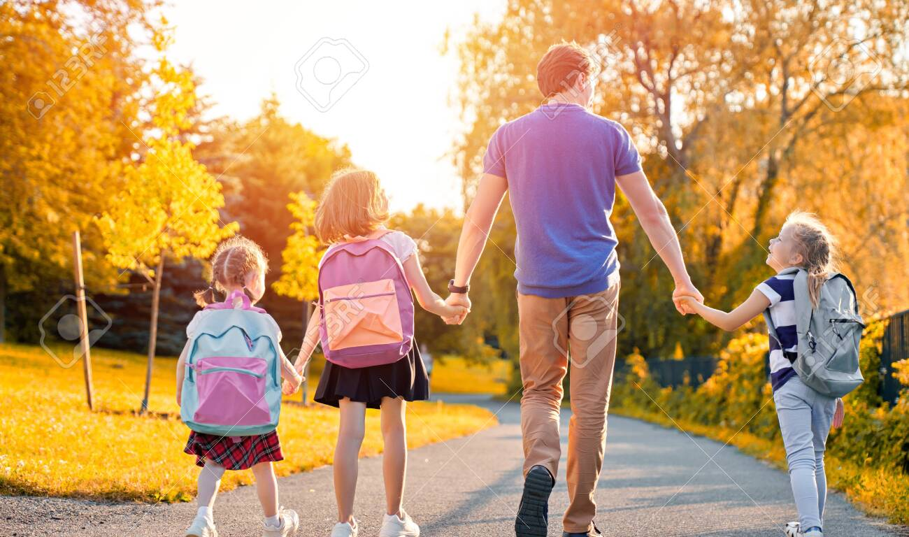 Parent and pupils of primary school are going hand in hand. Man and girls with backpacks behind backs. Beginning of lessons. First day of fall. - 127778106