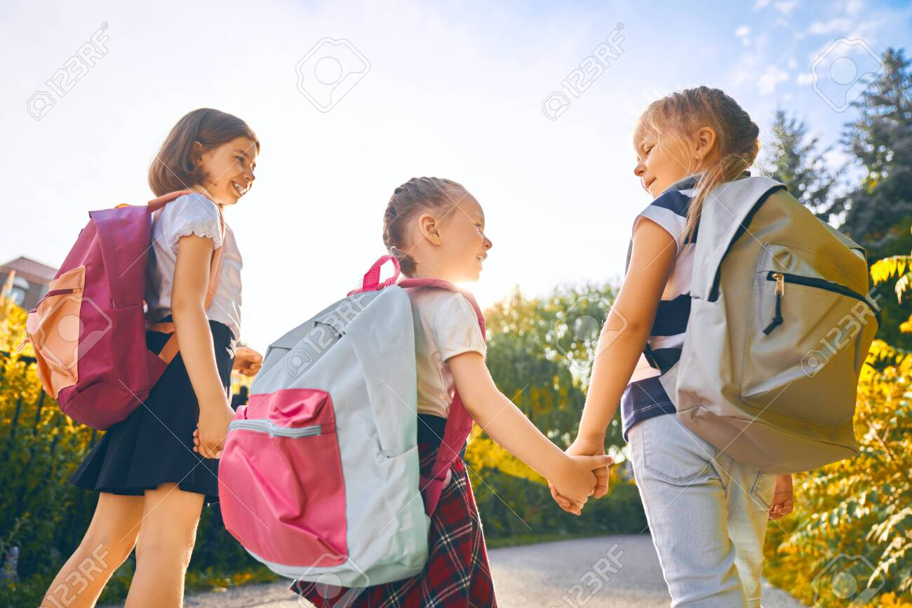 Pupils of primary school. Girls with backpacks outdoors. Beginning of lessons. First day of fall. - 127778105