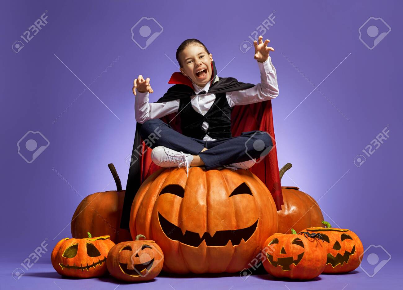 Happy Halloween! Cute little Dracula with a pumpkin on purple - 129603333